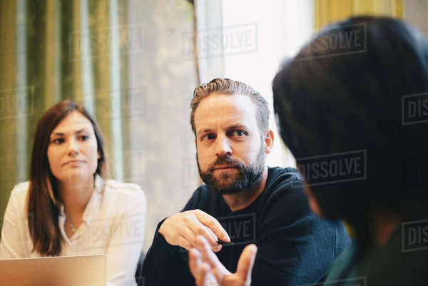 Confident businessman looking at female colleagues during board room meeting Royalty-free stock photo