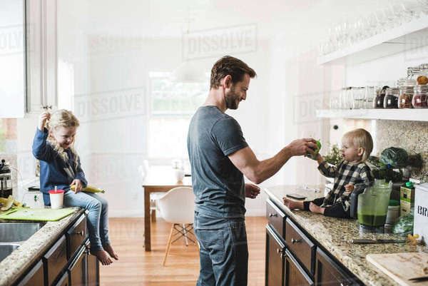 Girl looking at father feeding sister in kitchen at home Royalty-free stock photo