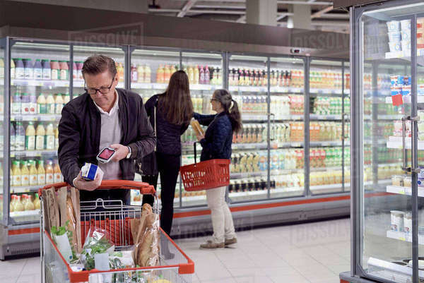 Mature man scanning juice box with reader against women buying at refrigerated section in supermarket Royalty-free stock photo