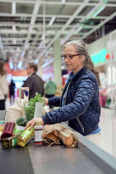Mature woman standing with groceries and bag at checkout counter in supermarket Royalty-free stock photo