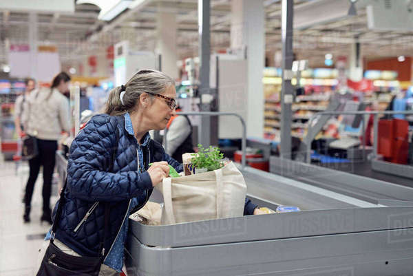 Mature woman putting groceries at checkout counter in supermarket Royalty-free stock photo