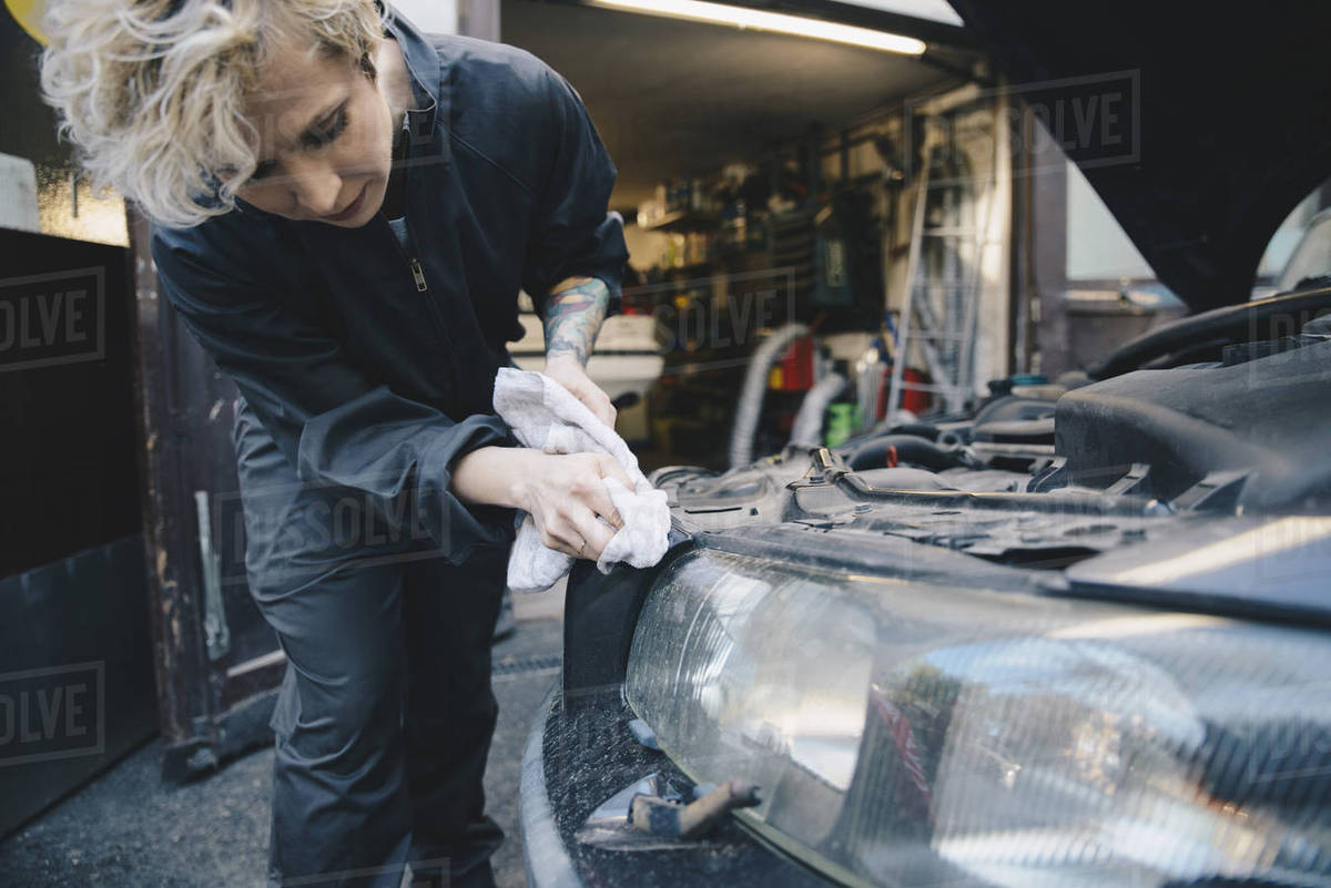 Female Mechanic Cleaning Car Headlight Outside Auto Repair Shop