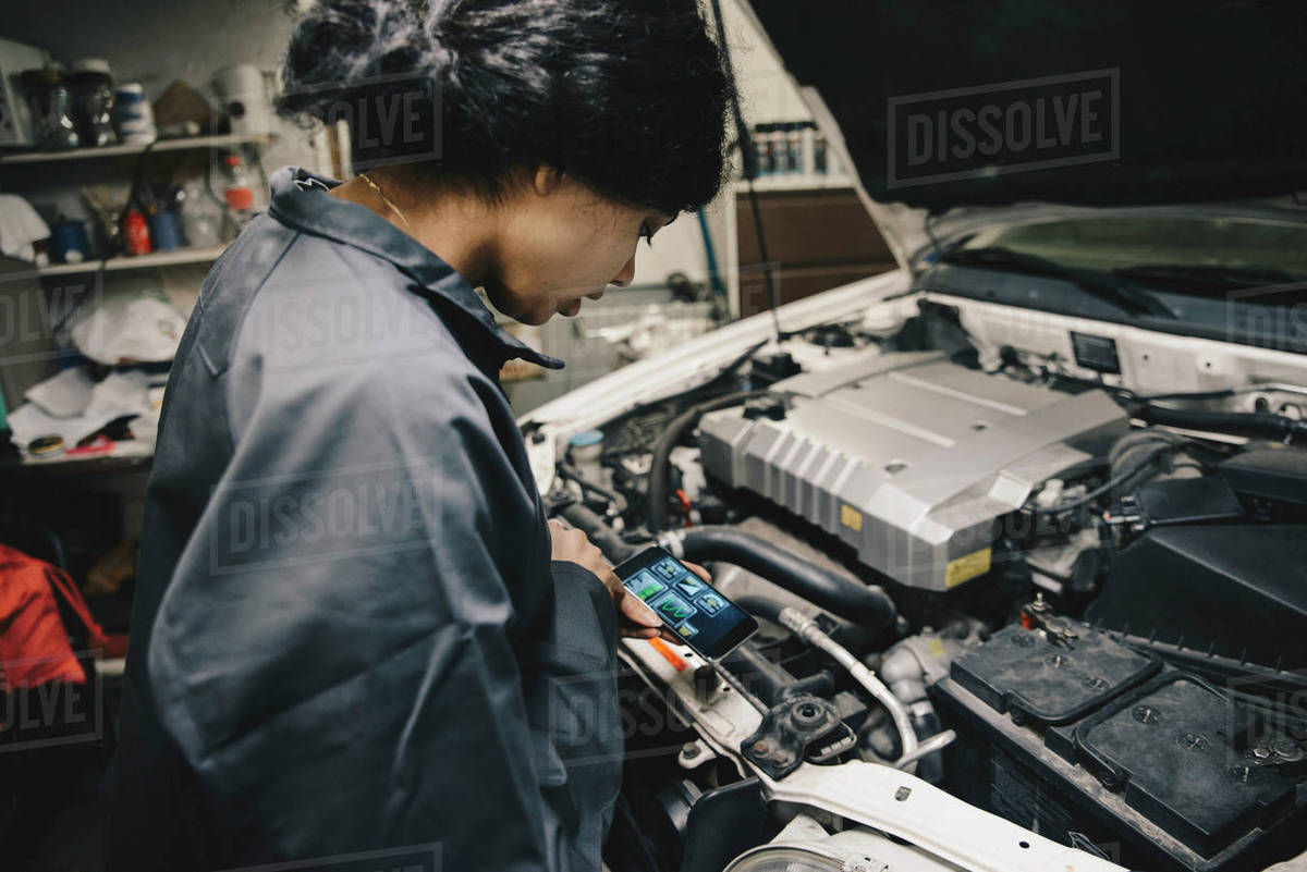 Female Mechanic Using Lication On Smart Phone While Standing By Open Car Hood