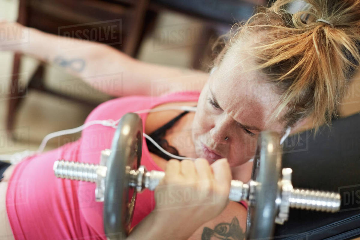 Determined disabled woman lifting weights at home stock photo