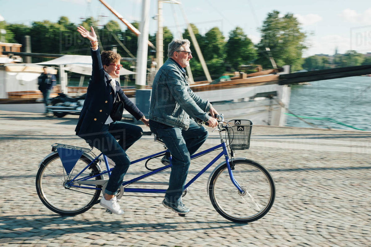 Full length side view of senior couple riding tandem bike on road in city  during vacation stock photo