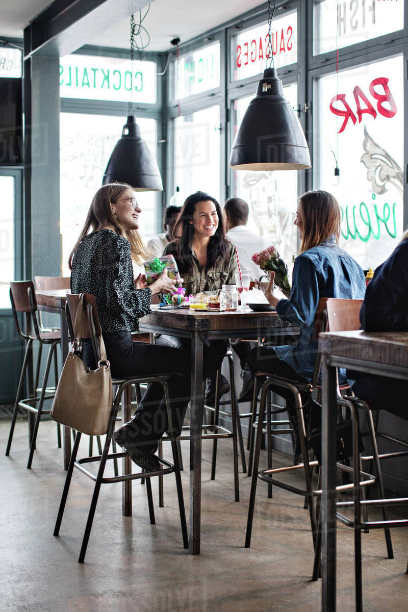 Full Length Of Smiling Female Friends Sitting With Birthday Presents At Dining Table In Restaurant