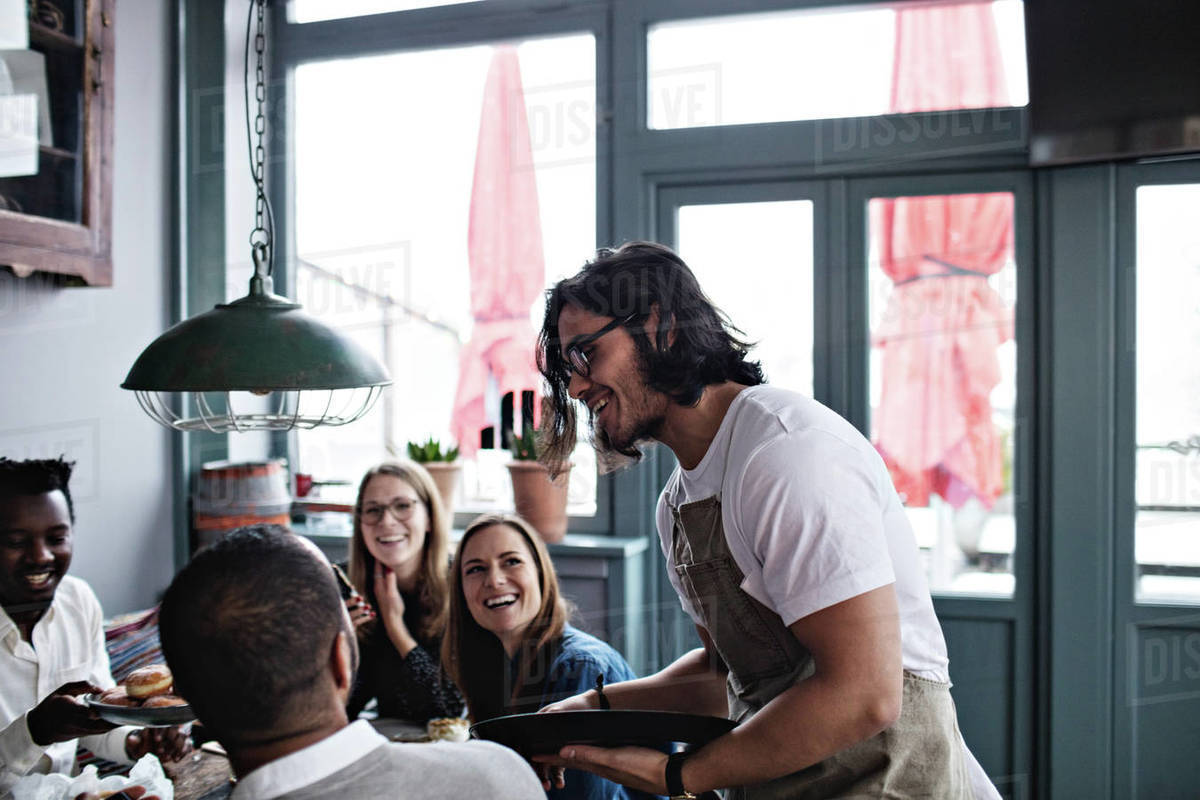 Smiling waiter talking to happy customers at restaurant stock photo