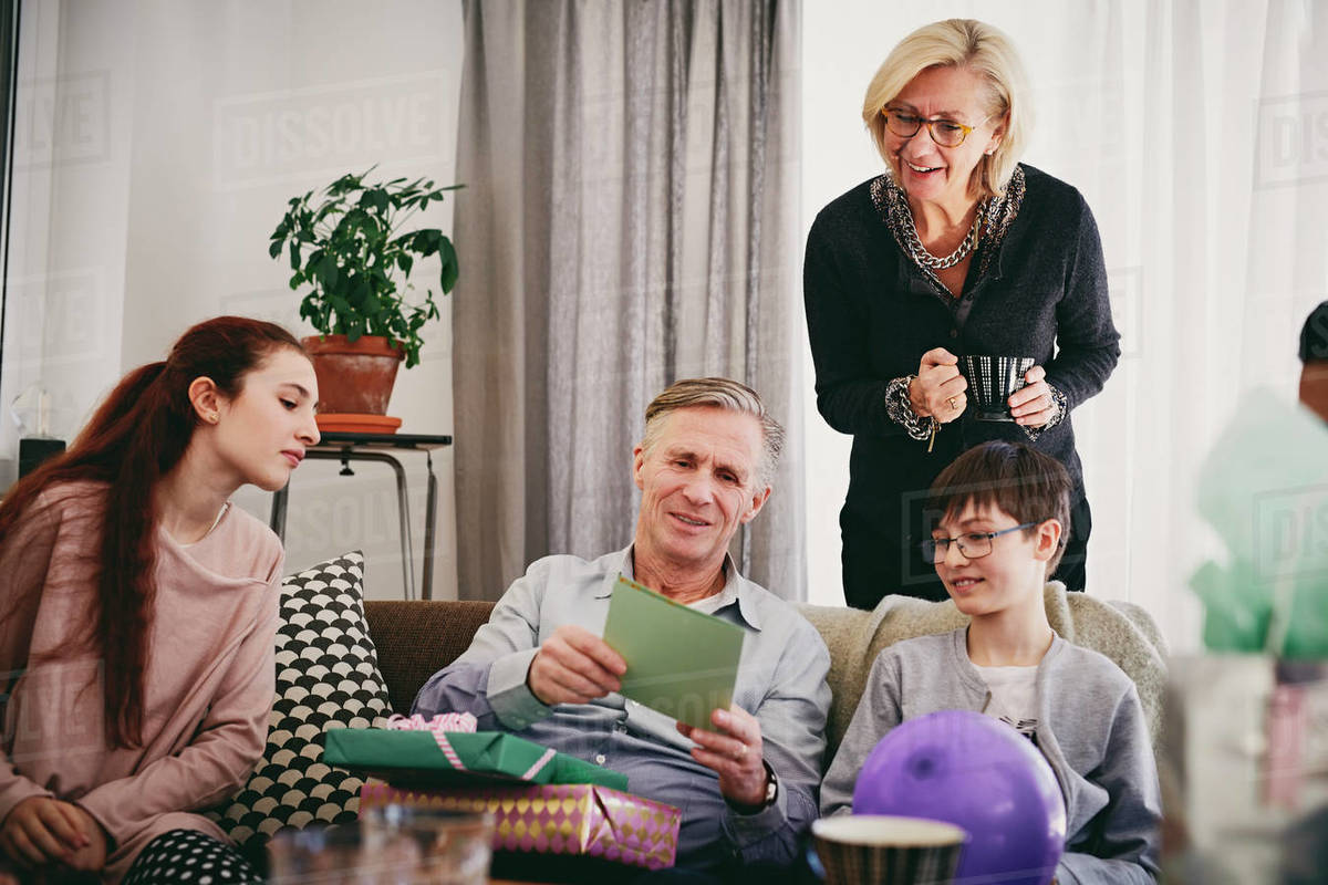 Grandfather With Birthday Presents Reading Greeting Card To Family