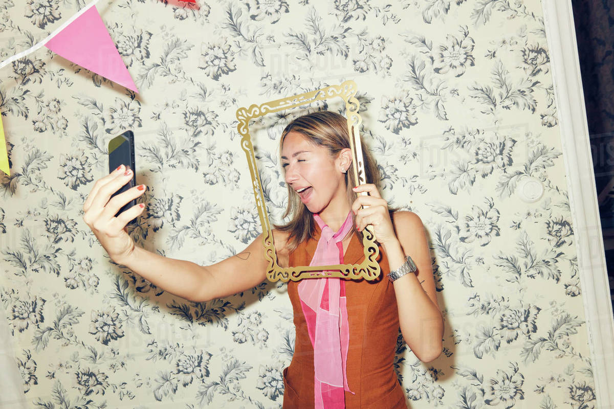 Cheerful young woman taking selfie through picture frame while winking at smart phone against wallpaper during party in Royalty-free stock photo