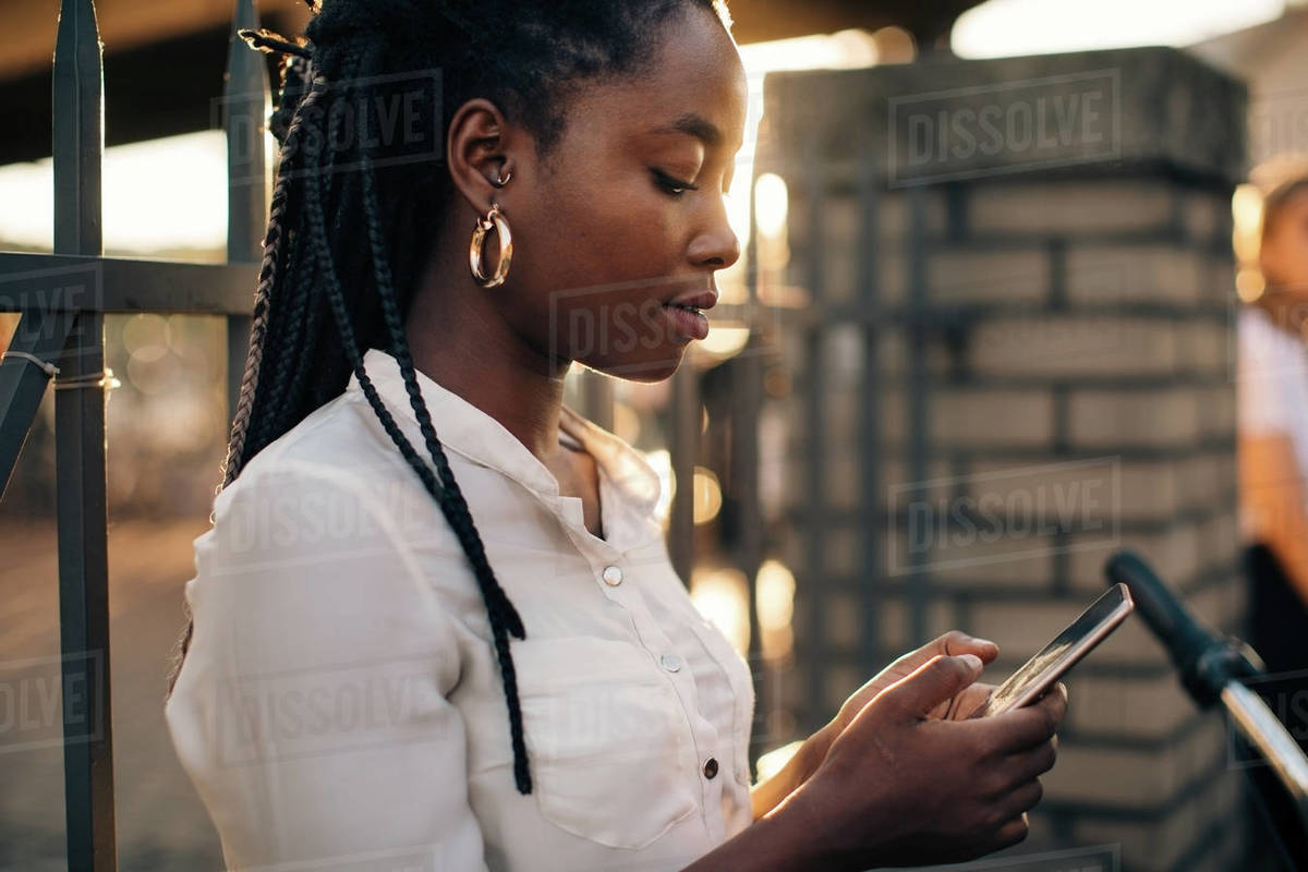 Young woman text messaging through smart phone while standing against fence in city Royalty-free stock photo