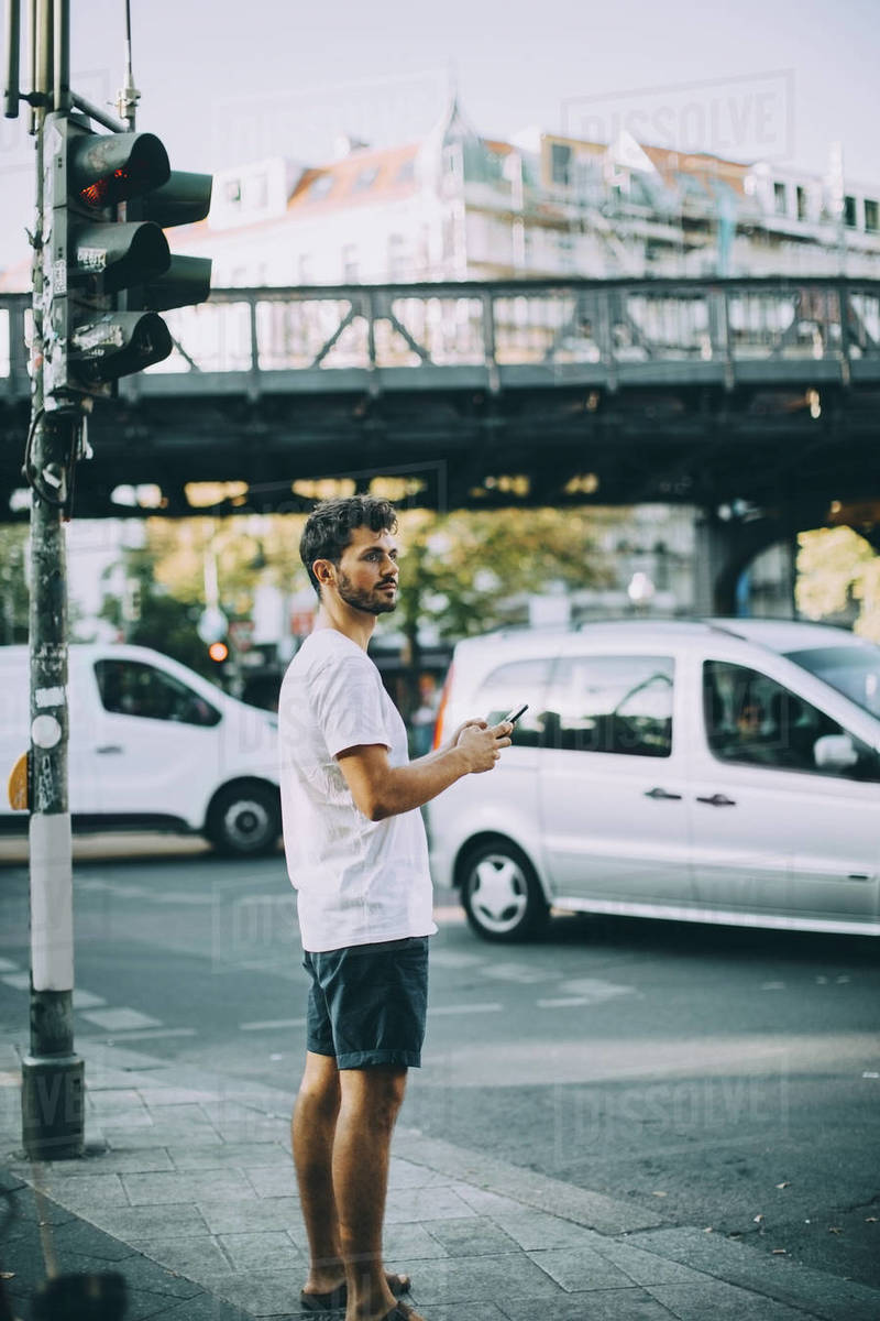 Side view of young man holding mobile phone while standing on sidewalk in city Royalty-free stock photo