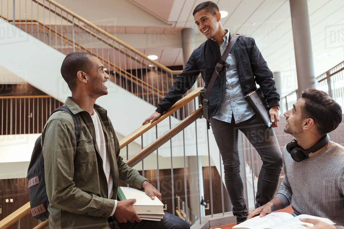 Happy students talking on steps in university Royalty-free stock photo