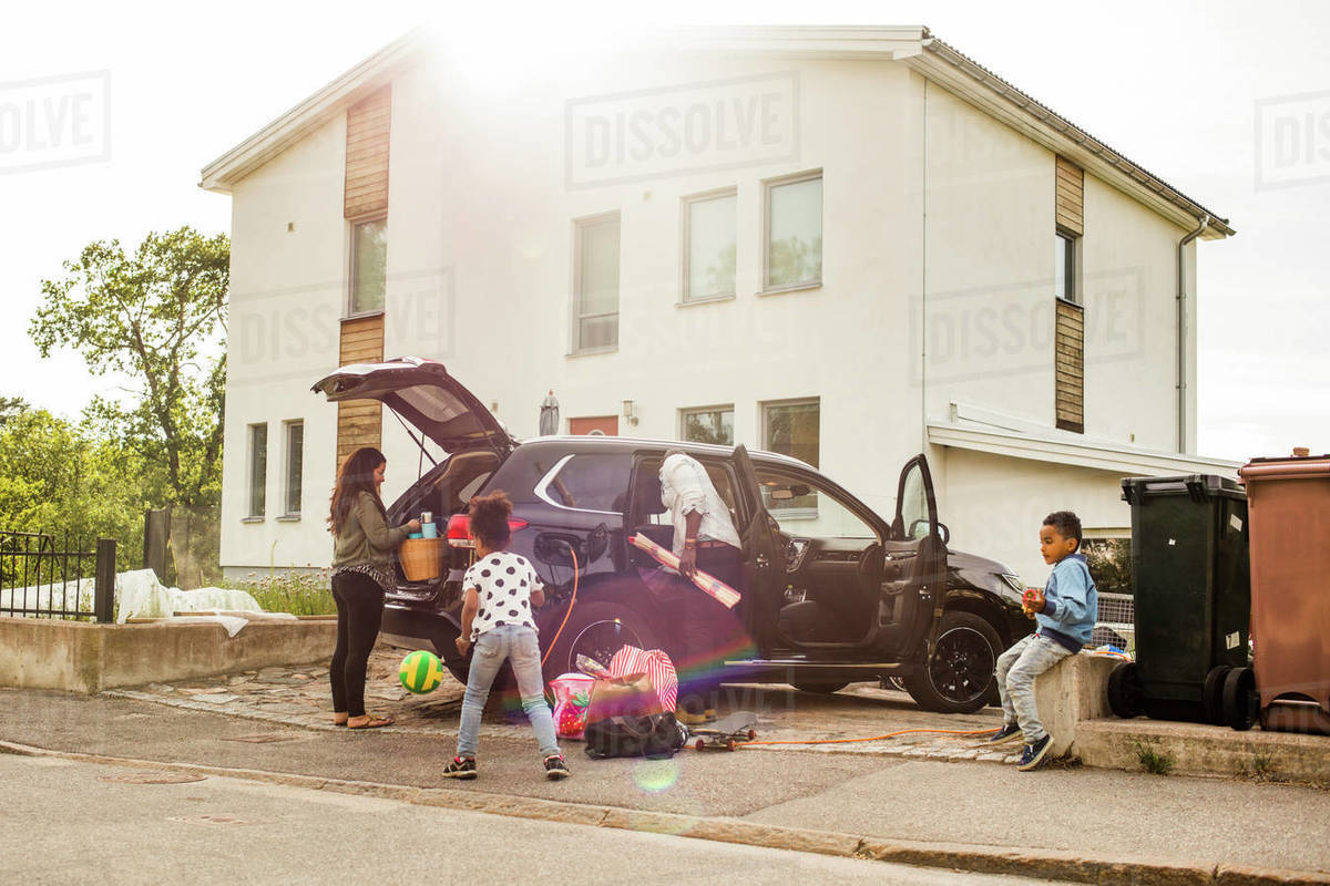 Family with electric car on driveway against house Royalty-free stock photo