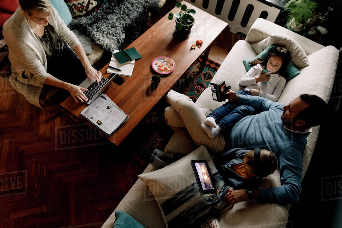 High angle view of family using various technologies in living room at home Royalty-free stock photo