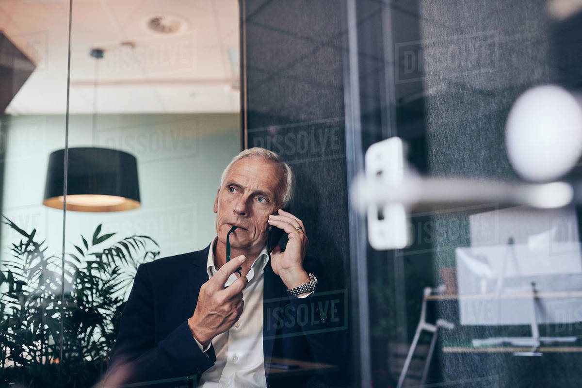 Thoughtful male manager talking on smart phone while looking away at creative office Royalty-free stock photo