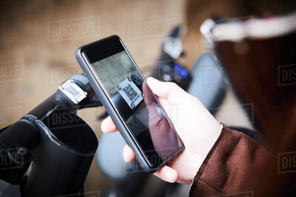 Cropped image of teenage boy using mobile phone over electric push scooter Royalty-free stock photo