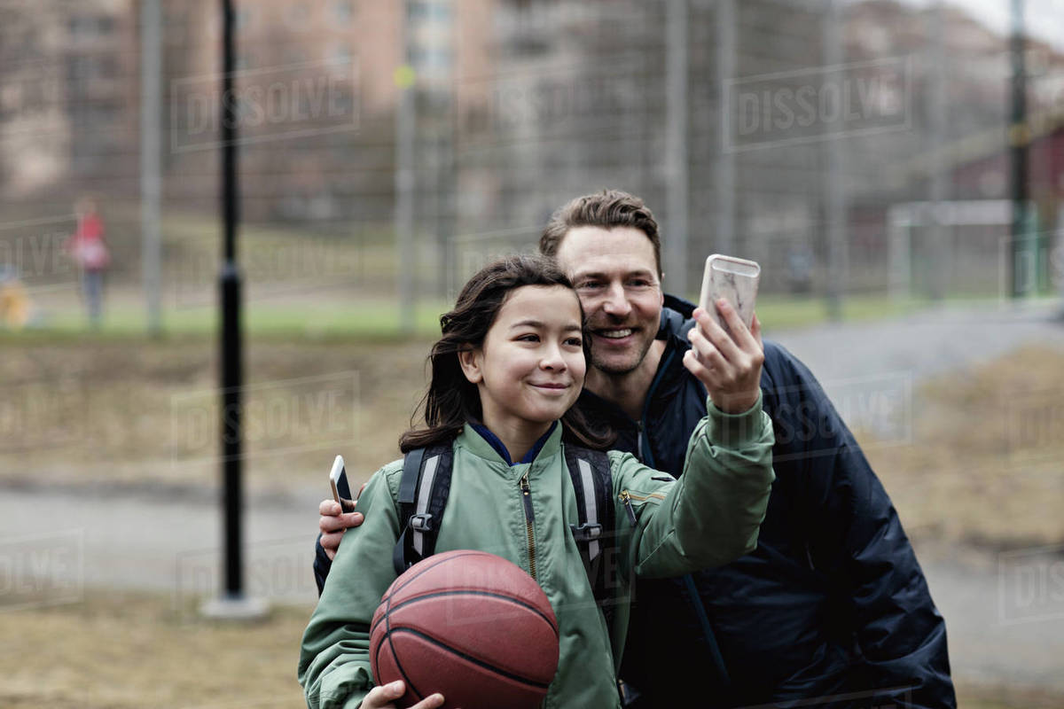 Smiling son taking selfie with father after basketball practice in winter Royalty-free stock photo