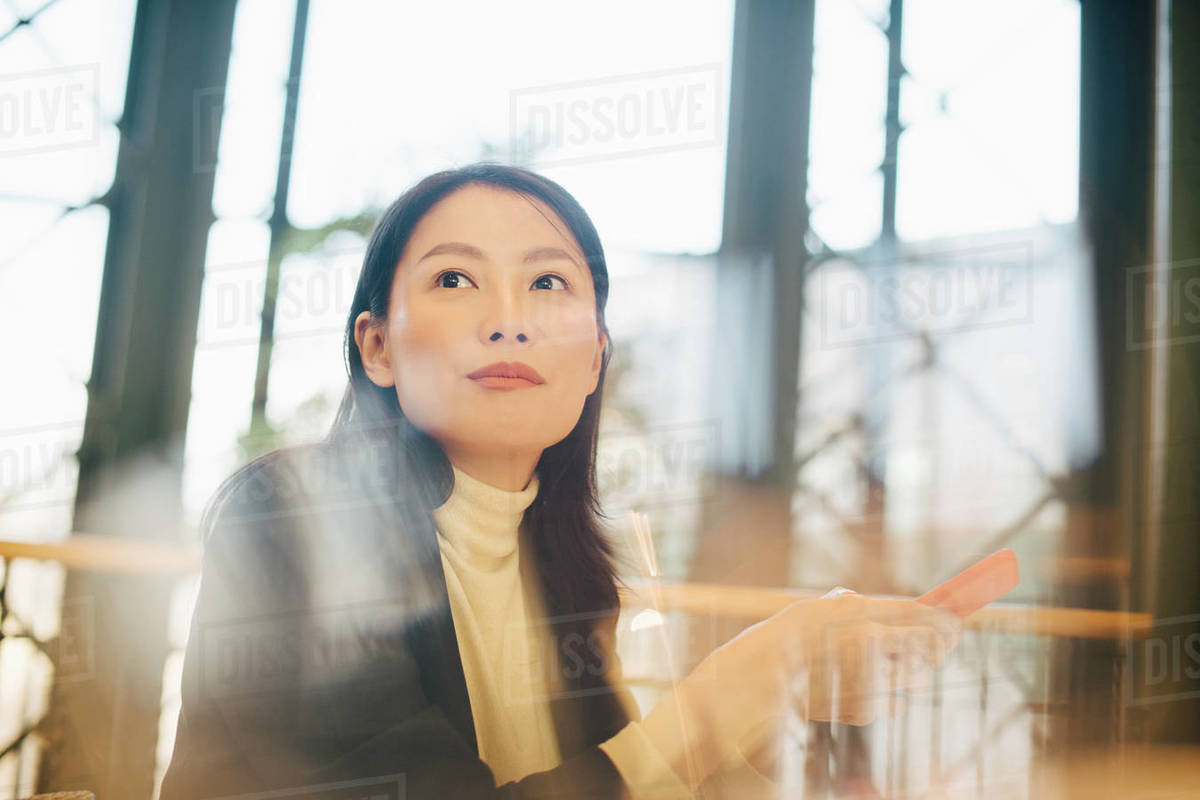 Confident businesswoman holding smart phone while looking away in office cafeteria Royalty-free stock photo