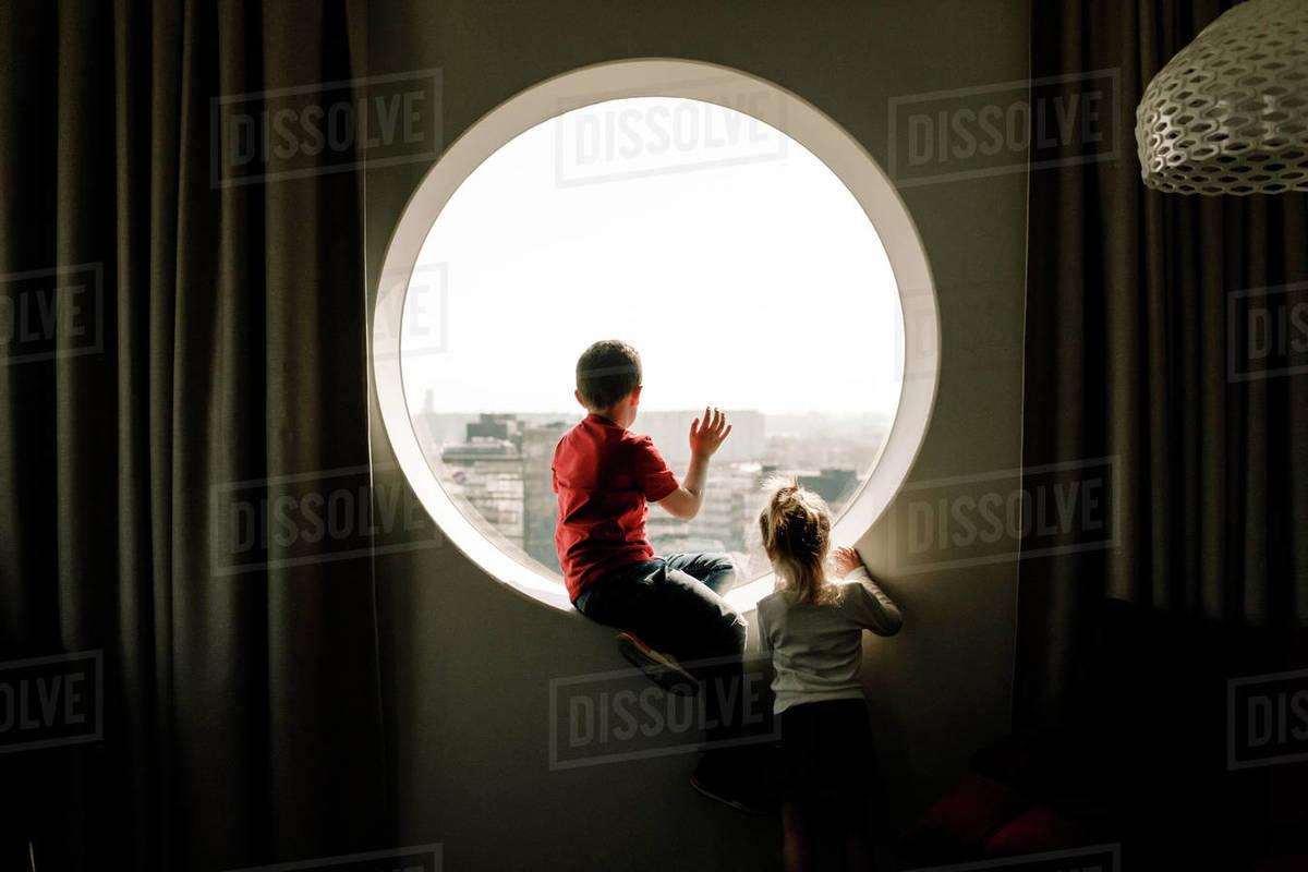 Siblings by window in hotel room Royalty-free stock photo