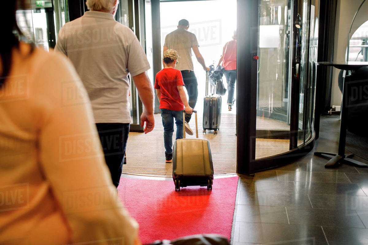 Rear view of family walking at hotel exit Royalty-free stock photo