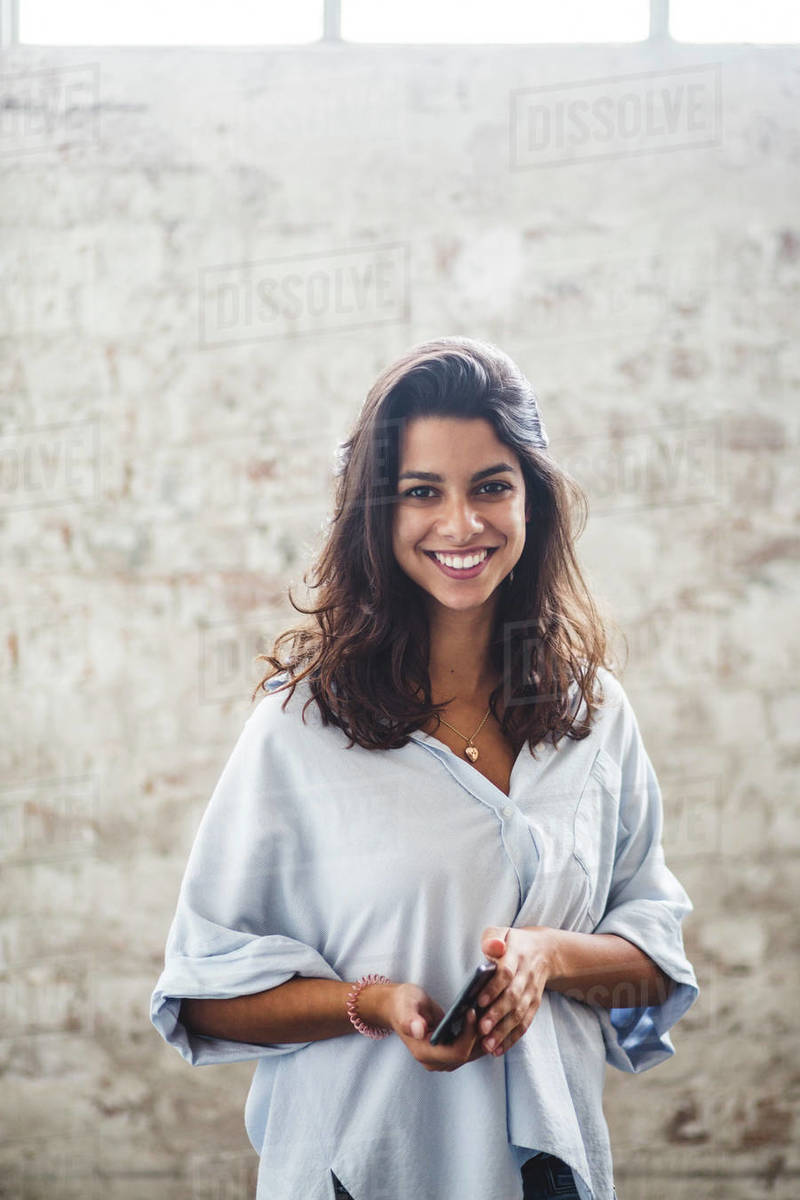 Portrait of smiling young female computer programmer holding smart phone standing against brick wall at creative office Royalty-free stock photo