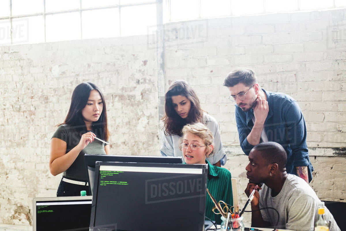 Confident young professionals planning while coding in computer at workplace Royalty-free stock photo