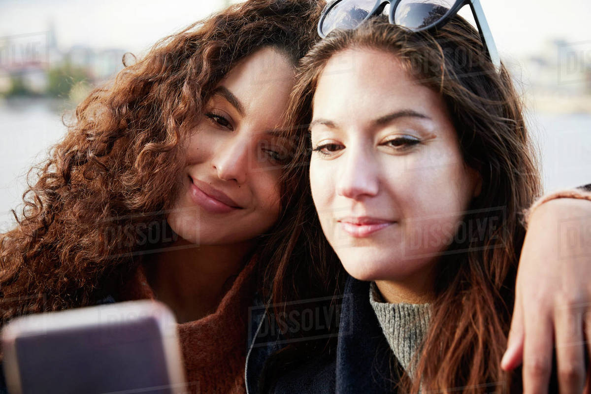 Lesbian couple taking selfie with mobile phone in city