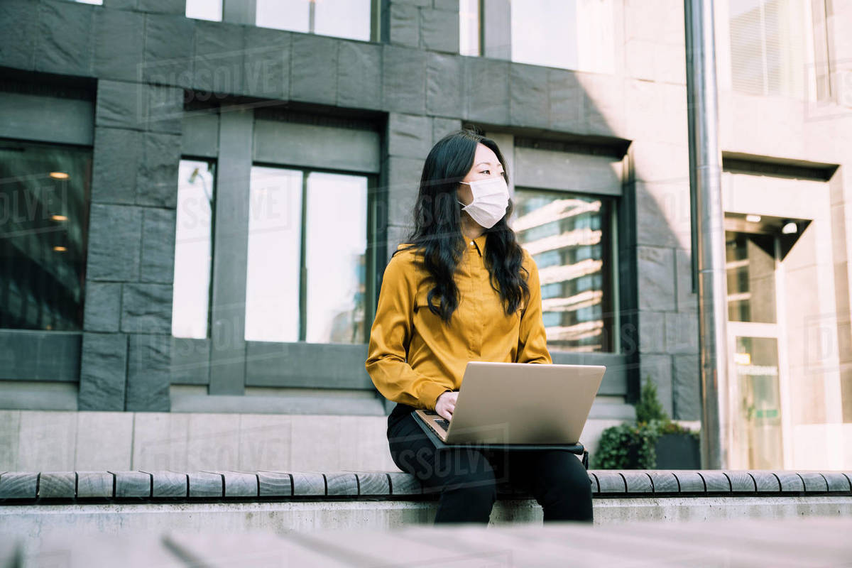 Businesswoman with laptop working outside wearing face mask Royalty-free stock photo