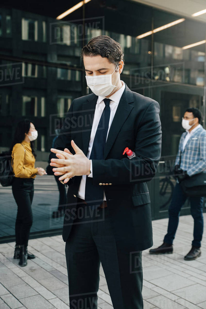 Businessman with face mask washing hands with hand sanitiser Royalty-free stock photo