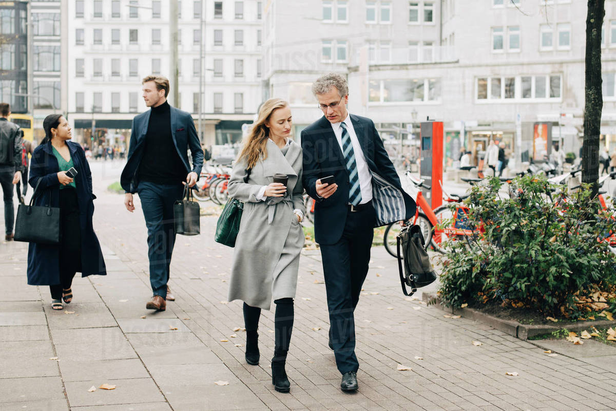 Businessman showing smart phone to female colleague while walking in city Royalty-free stock photo
