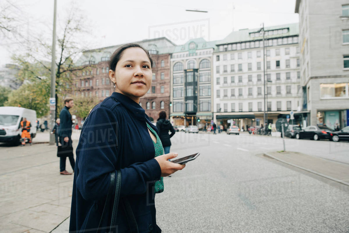 Side view of female entrepreneur with phone standing in city Royalty-free stock photo