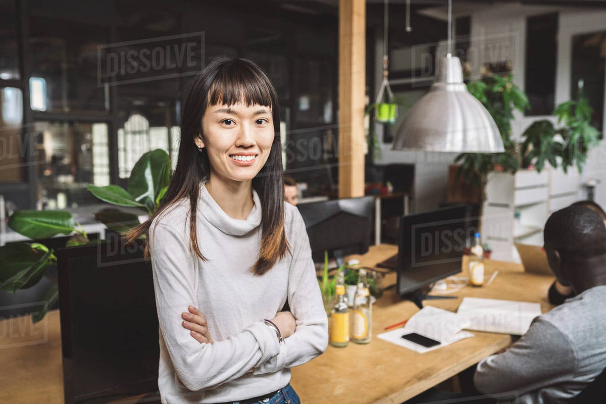 Portrait of smiling businesswoman with arms crossed at workplace Royalty-free stock photo