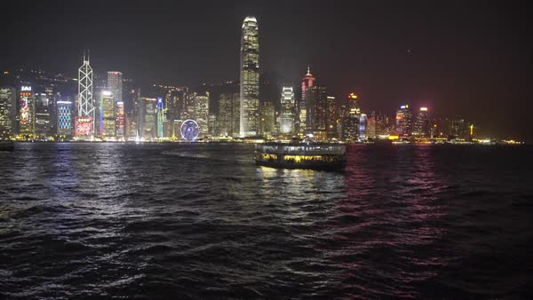 Hong Kong Island panorama with Star Ferry boats crossing Victoria Harbour in the early evening Royalty-free stock video