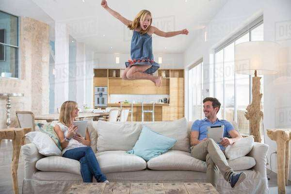 Girl jumping mid air from living room sofa whilst parents use digital tablet Royalty-free stock photo