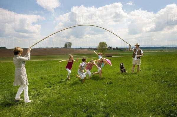 Happy family jump roping in countryside Royalty-free stock photo