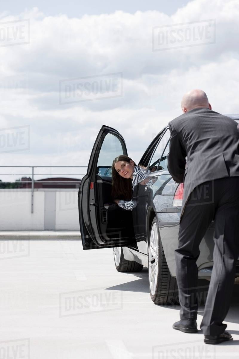 man pushing car woman observing stock photo dissolve