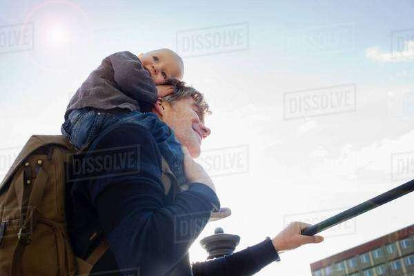 Father giving baby daughter shoulder ride in city Royalty-free stock photo
