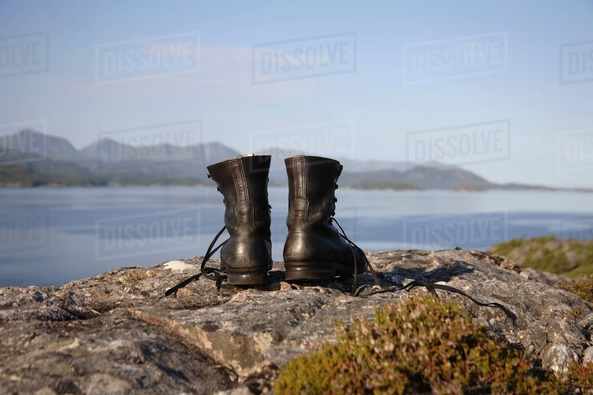 Hiking boots on cliff by the sea Royalty-free stock photo