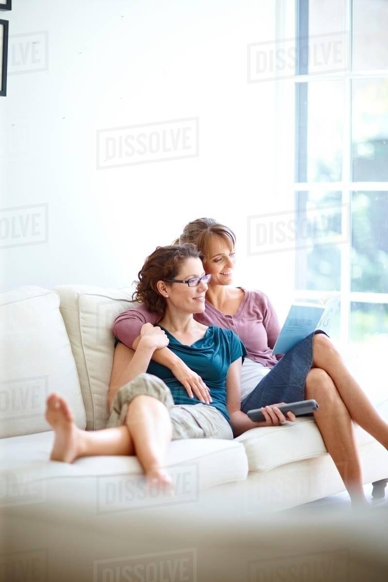 Two Women Cuddling On Sofa