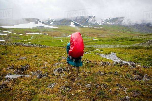 Rear view of young man hiking in valley, Ural mountains, Russia Royalty-free stock photo