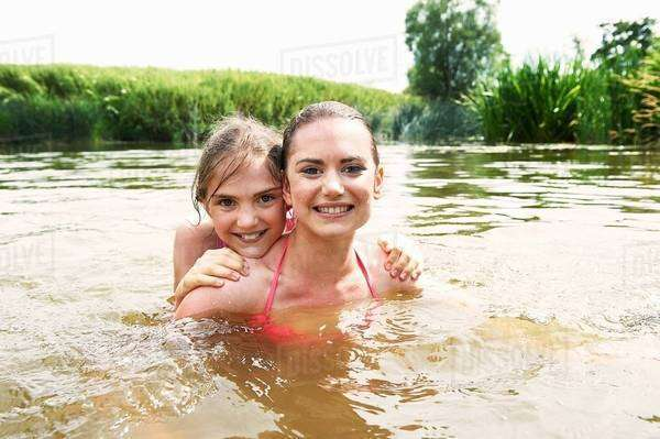 Portrait of teenage girl and sister swimming in rural lake Royalty-free stock photo