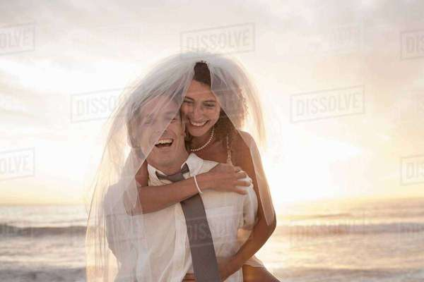 Bride riding piggyback on groom on beach against sunset Royalty-free stock photo
