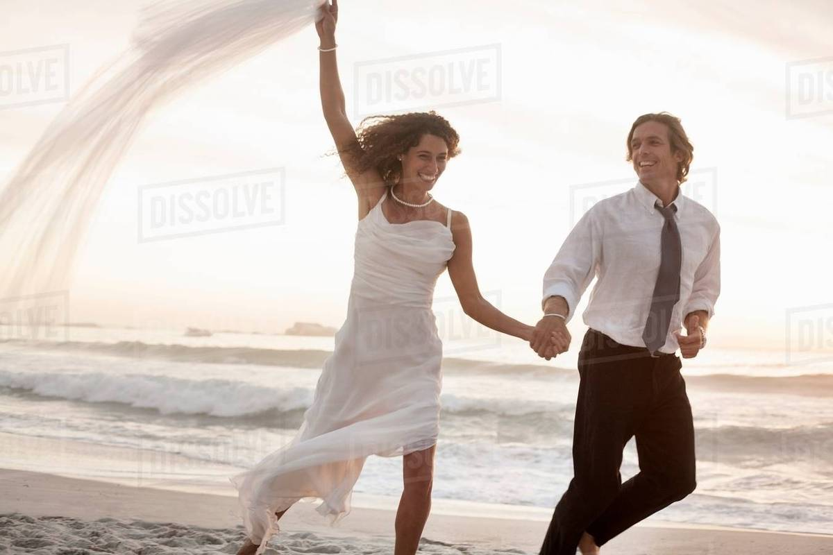 Brilliant Bride And Groom Running On Beach Against Sunset Stock Photo Download Free Architecture Designs Scobabritishbridgeorg