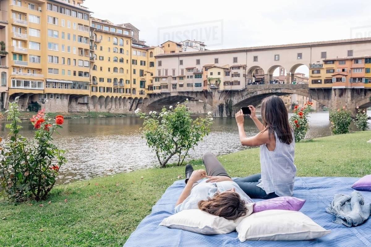 Camera A Ponte.Lesbian Couple On Blanket Using Digital Camera To Photograph Ponte Vecchio Over River Arno Florence Tuscany Italy Stock Photo