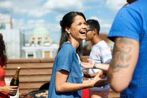 Female and male friends laughing and chatting at rooftop barbecue Royalty-free stock photo