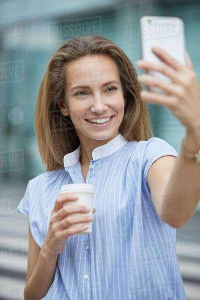 Young woman using smartphone to take selfie smiling Royalty-free stock photo