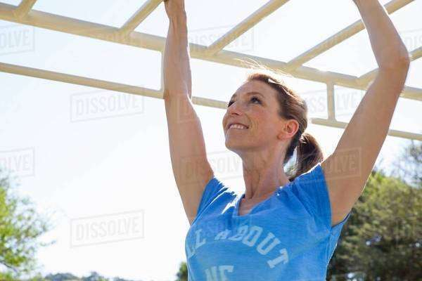 Mid adult woman training on monkey bars in park Royalty-free stock photo