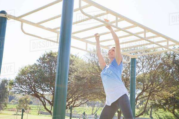 Mid adult woman training in park on monkey bars Royalty-free stock photo