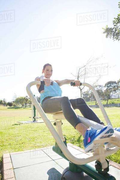 Mid adult woman in park training on rowing machine Royalty-free stock photo