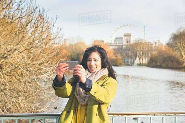Young woman in St James's Park using smartphone to take selfie, smiling, London, UK Royalty-free stock photo